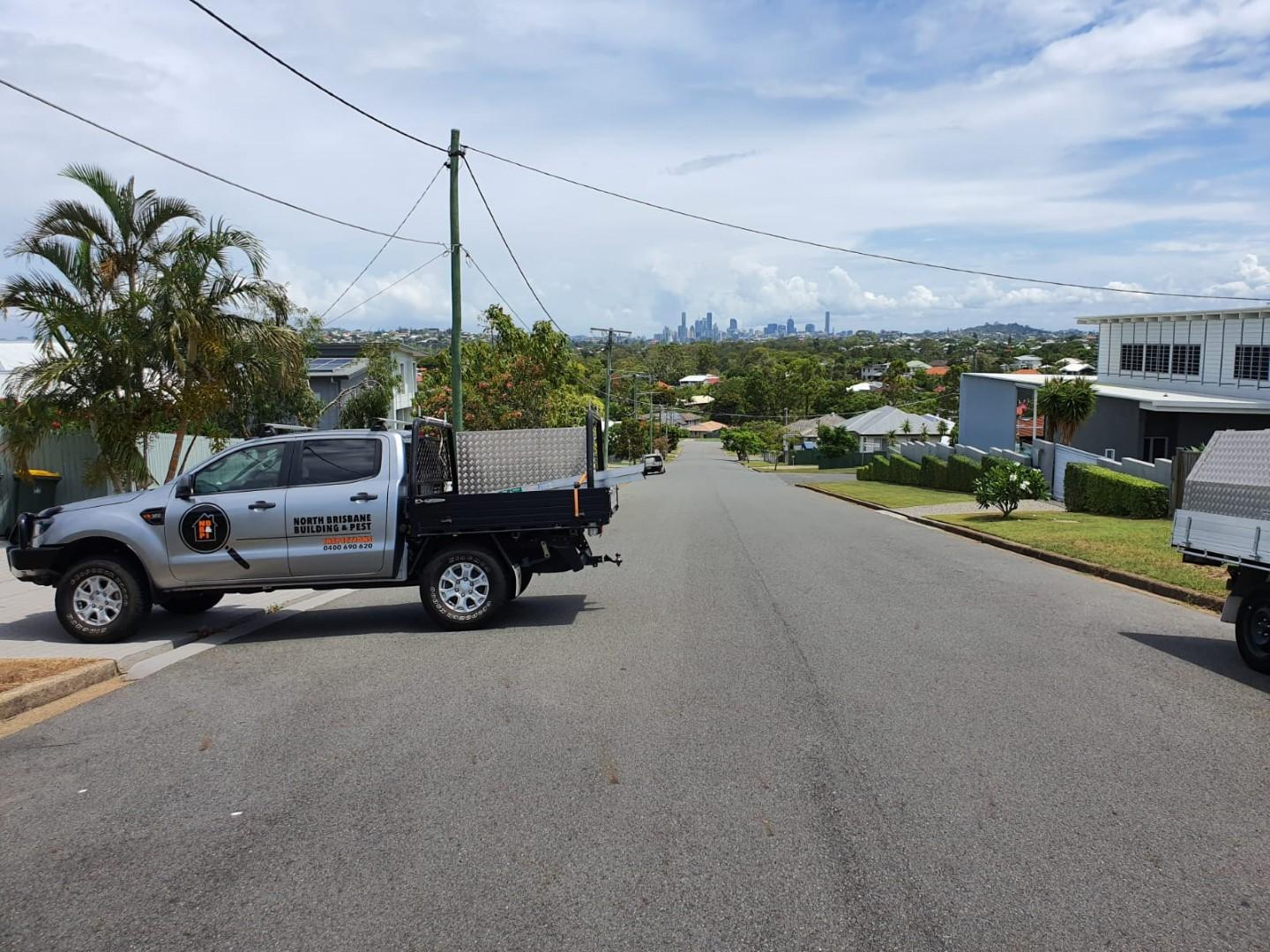 Brett's Building inspection Ute on the driveway of a building inspection house with views of Brisbane CBD in the background